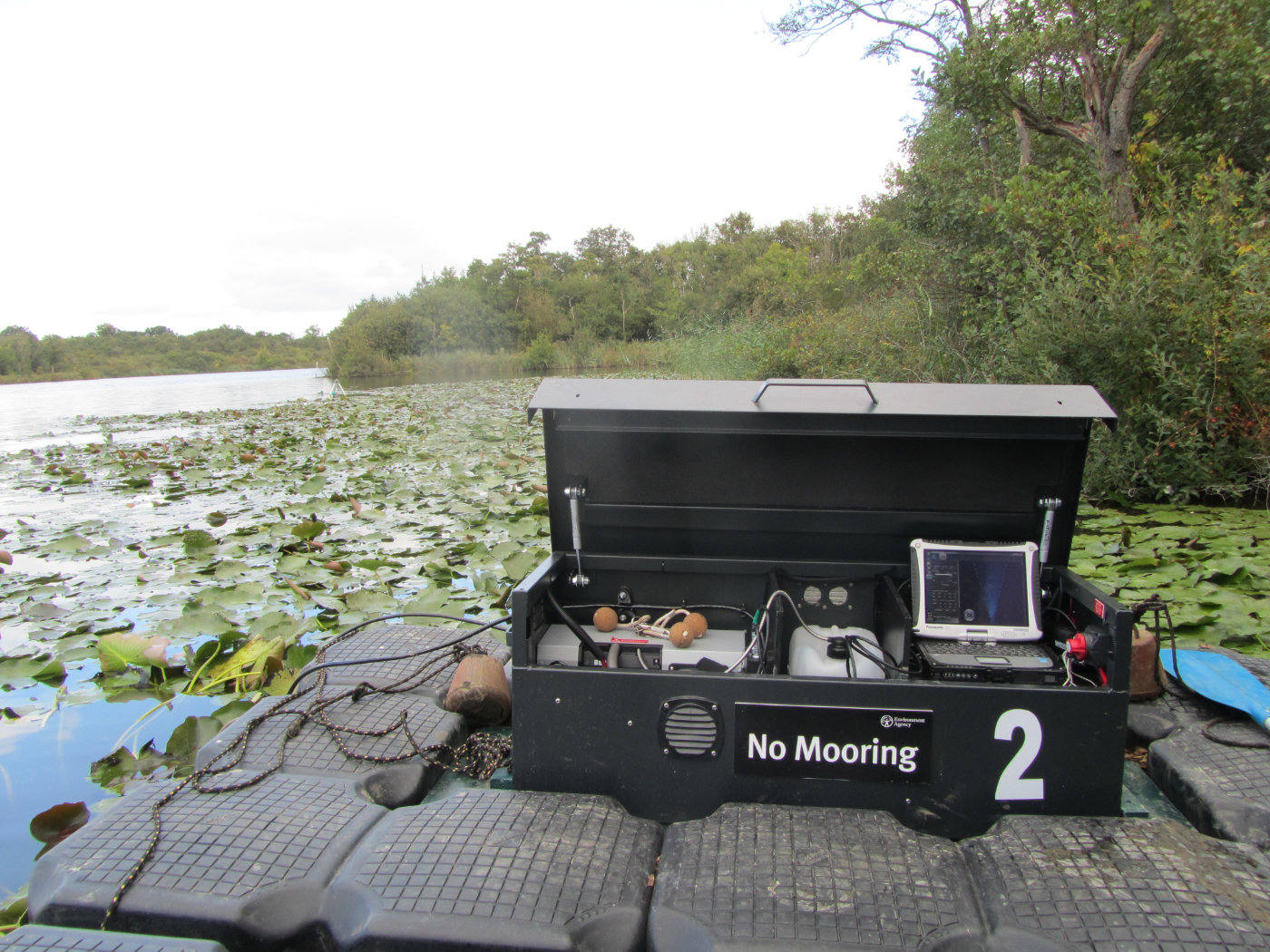 conservation equipment on a jetty next to water covered in lily pads