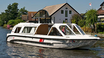 A man cruising on the Norfolk Broads on board a rented boat